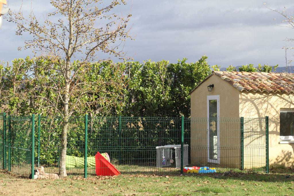 Petit bâtiment situé à droite de la photo et parc à chiots dans lequel sont disposés des jeux d'éveil pour les chiots